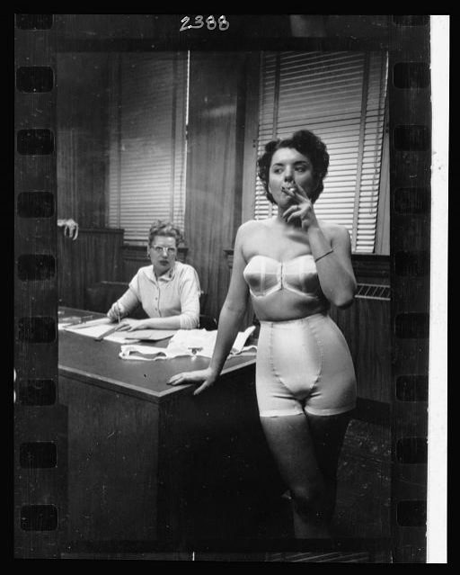 21.-Lingerie-model-wearing-a-girdle-and-strapless-bra-smoking-in-an-office-in-the-background-a-woman-sits-at-a-desk.jpg