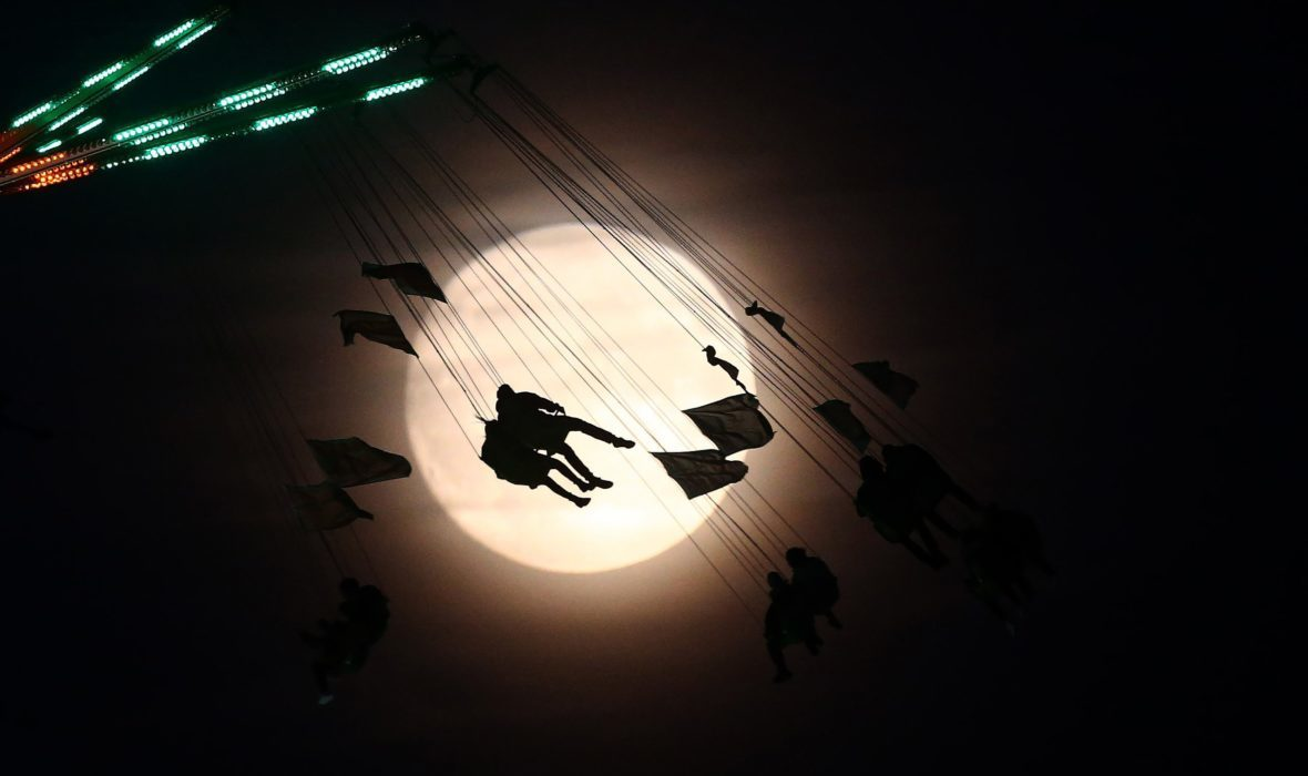"People on a fair ride are silhouetted against the moon a day before the ""supermoon"" spectacle in London, Britain, on Nov. 13, 2016."