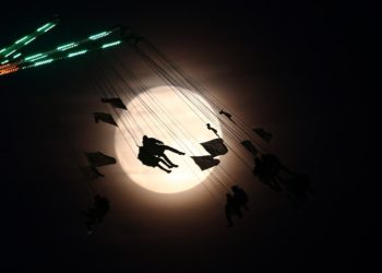 People on a funfair ride are silhouetted against the moon a day before the supermoon spectacle, in London