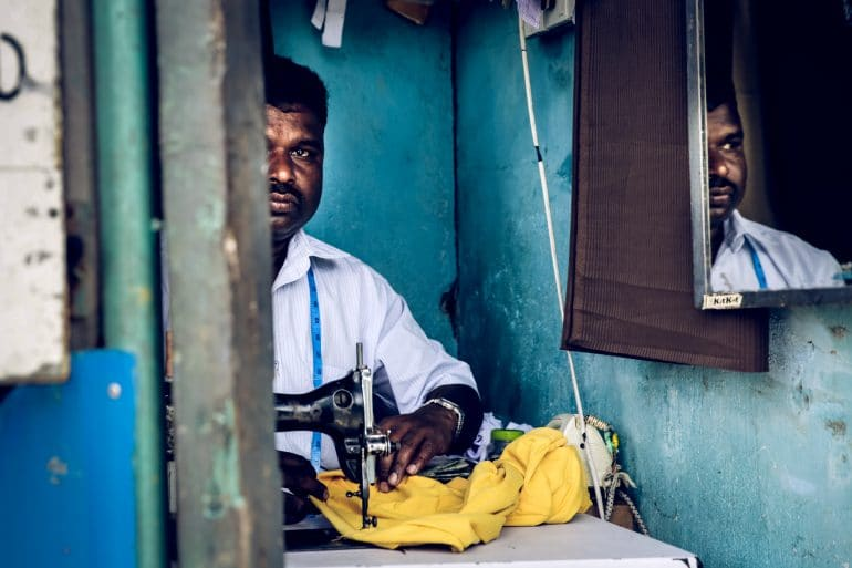 Man sewing in the middle of the street