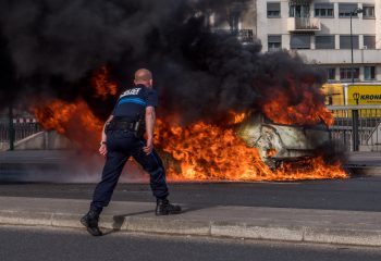Fired up policeman trying to blow out a fire