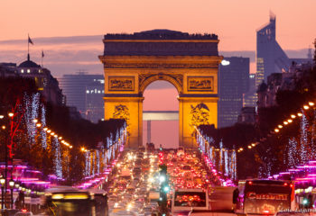 Arc de Triomphe and Champs-Elysées avenue with christmas 2011 lights at dusk, La Defense financial district in the background.