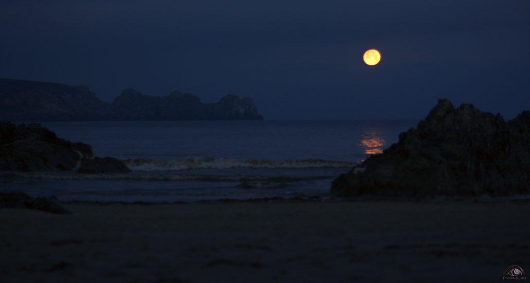 Lune orange sur l'océan à l'aube