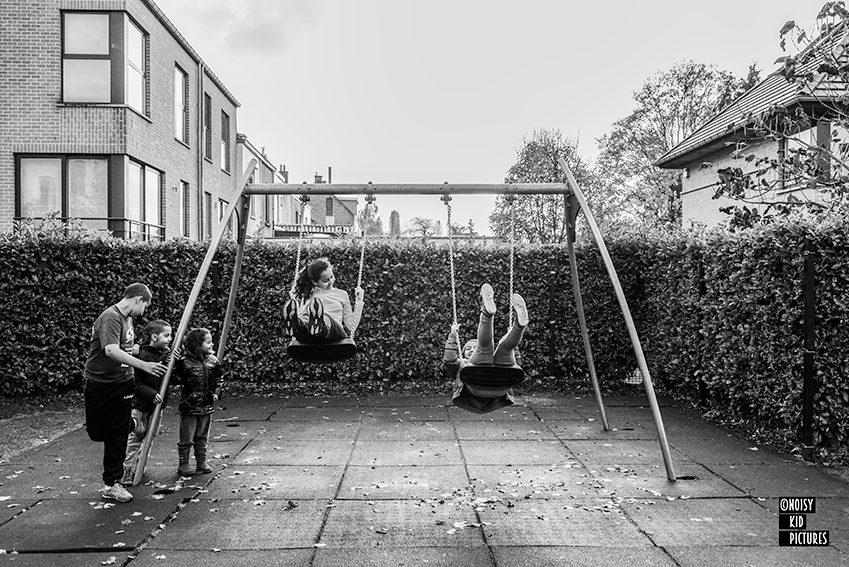 Happy kids swinging on playground